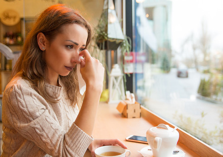 Young girl in sorrow crying after breakup sitting with cup of tea at table in cafeteria near window