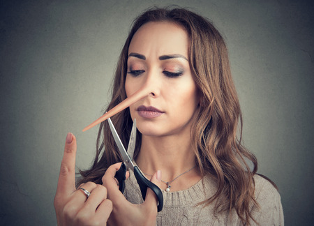 Girl having long nose of liar and trickster trying to change and cut nose off with scissors