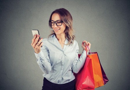Beautiful woman shopping online checking prices on mobile phone. Fashion girl with colorful bags looking at cellphone.