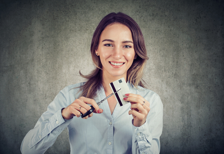 Cheerful young business woman looking happily at camera done with credit cards.
