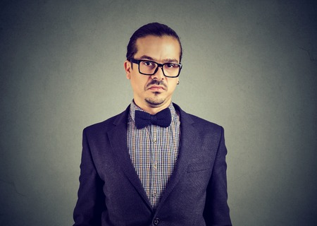 Young elegant man in glasses looking skeptically at camera full of doubts on gray background Stok Fotoğraf