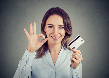 happy young business woman with credit card giving ok hand sign gesture
