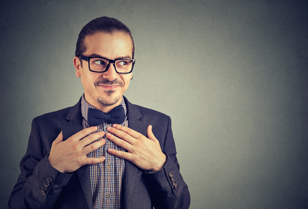 Young crazy man in glasses and suit looking nerdy away holding hands on chest in shyness on gray background Stock Photo