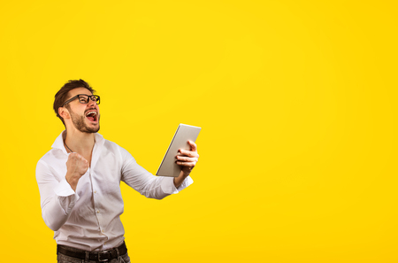 Cheerful bright hipster man holding fist up while screaming with happiness of win on yellow background and holding tablet