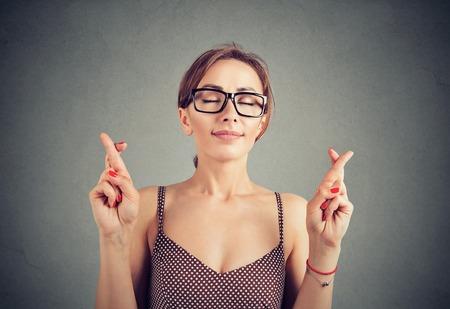 Nette junge Frau in Gläsern kreuzt Finger und macht einen Wunsch