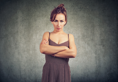 Young woman in dress holding hands crossed and looking at camera with anger and complaint on gray background Imagens