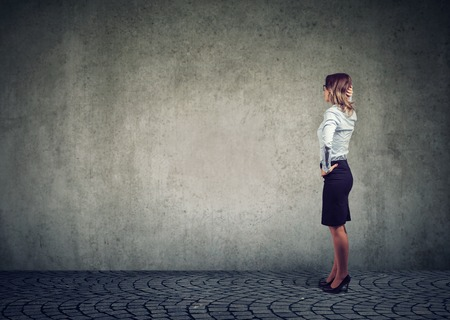 Side view of businesswoman standing in front of gray wall and contemplating in effort to solve problem