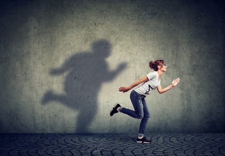 Woman running away from her fat shadow on the wall. Body weight control concept 版權商用圖片