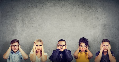 Eine Gruppe multikultureller Menschen, Frauen und Männer, die sich die Ohren zuhalten, wollen sich nicht zuhören
