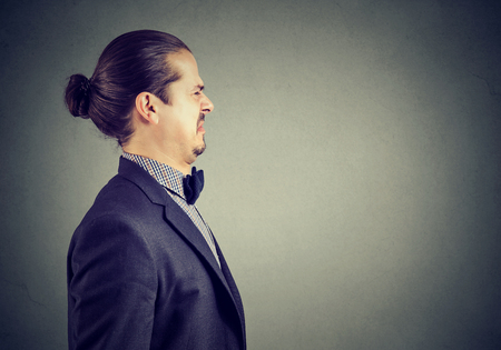 Side portrait of a disgusted young business man
