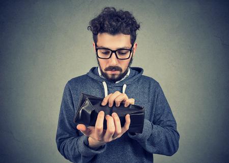 Sad man with no money holding an empty wallet Foto de archivo