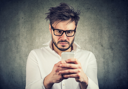 stunned man, surprised offended, shocked by what he sees on his smartphone Foto de archivo