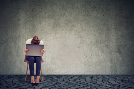 Anonymous woman sitting on chair with laptop on knees and looking desperate in crisis against gray wall background Stock Photo