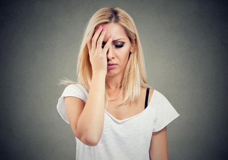 Casual young woman having problems and looking worried with stressed face expression on gray background.