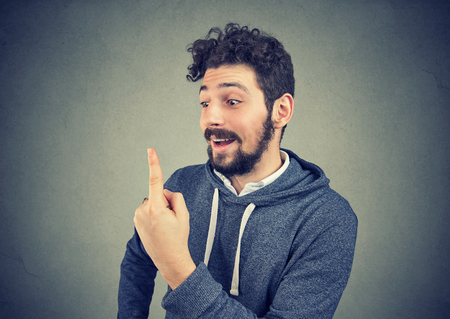 Excited funny man looking at his finger has double vision