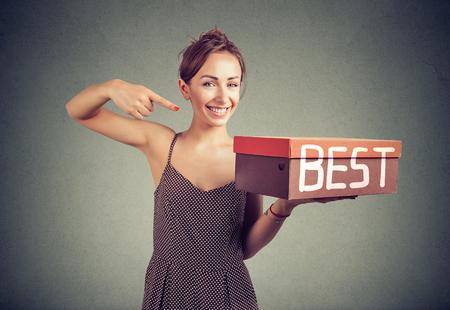 Smiling young saleswoman advertising best product Foto de archivo