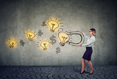 Business woman attracts bright ideas light bulbs with a big magnet