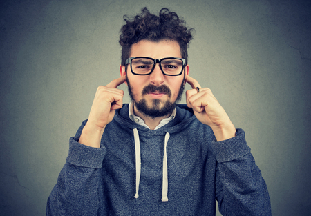 Annoyed young hipster man looking grumpy at camera and covering ears from noise avoiding loud noise and conflict situation on gray background 스톡 콘텐츠
