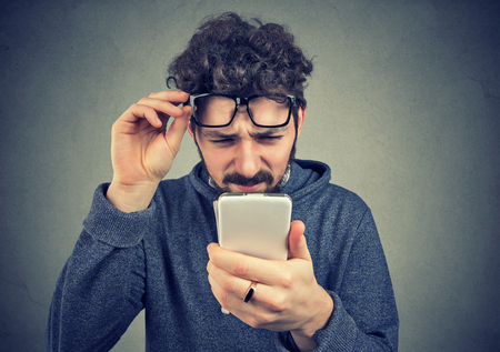 Closeup portrait of a man wearing glasses having trouble seeing cell phone has vision problems. Confusing technology Foto de archivo