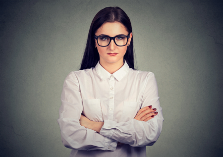 Young brunette in white shirt and glasses holding arms crossed and looking at camera strictly
