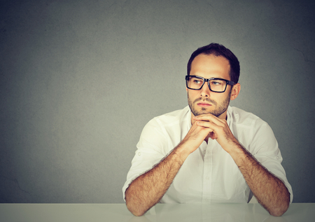 Adult sad man in white shirt and glasses sitting at table leaning on hands and thinking on gray background