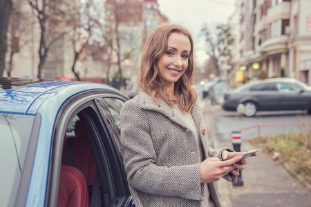 Happy woman using mobile phone standing beside her car