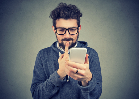 uomo perplesso pensando a cosa rispondere al messaggio di testo ricevuto sul telefono cellulare isolato su sfondo grigio muro. Linguaggio del corpo di reazione di espressione del viso