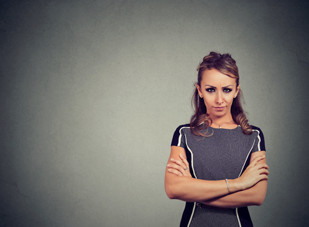Young offended woman with hands crossed looking at camera in dislike on gray background
