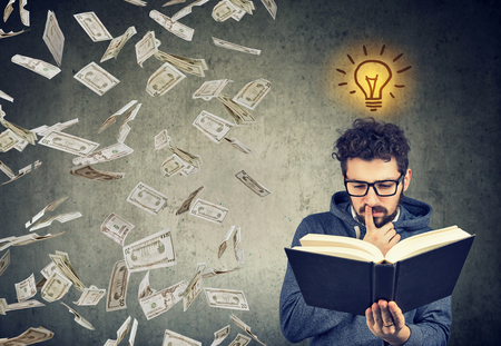 Man student reading a book has a bright idea how to earn money