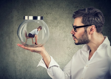 Businessman holding a glass jar with a young sad businesswoman trapped in it