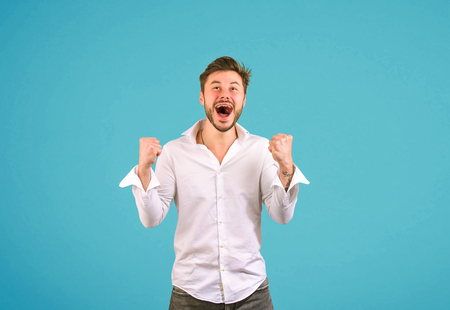 Excited handsome man in white shirt holding fists up and screaming with happiness on blue background Stock Photo
