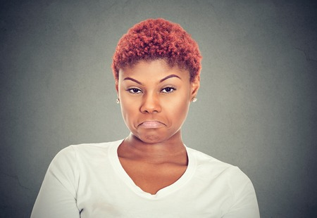 Displeased upset female frowns face as going to cry, being discontent and unhappy isolated on gray background. Disapointed woman has troubles