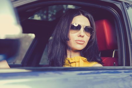 Beautiful modern brunette in sunglasses driving modern expensive car with confidence