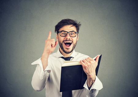 Young smart business man in glasses holding finger up excited with great idea while holding book on gray background
