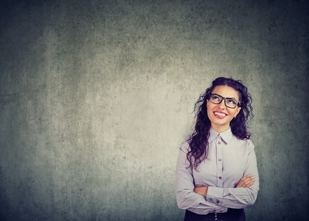 Portrait of a young cute woman wearing glasses and looking up in excitement thinking daydreaming on gray background Standard-Bild - 110123346