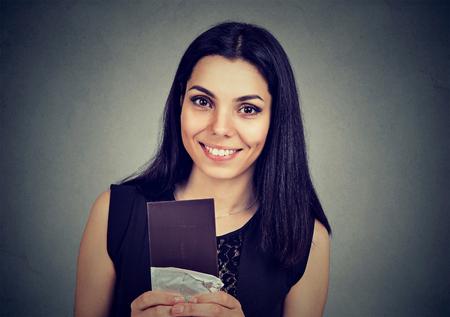 Portrait of a young beautiful girl holding a dark chocolate bar happy to enjoy the taste Standard-Bild - 110123351