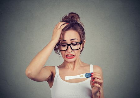 Portrait of a young shocked woman with positive pregnancy test Standard-Bild - 110068525