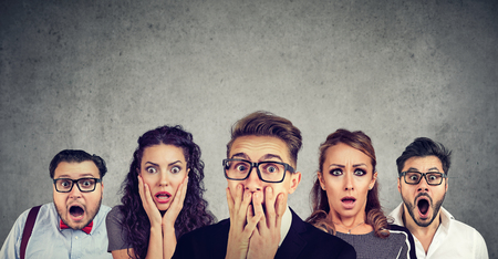 Shocked man in glasses and his scared friends pose against grey wall background. Standard-Bild - 110068529