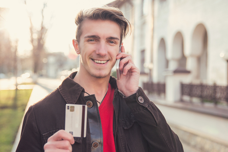 Happy young man speaking on smartphone while showing credit card Standard-Bild - 110068531