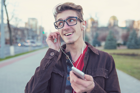 Happy young man in glasses holding smartphone and listening to music with headphones outdoors Standard-Bild - 110068534
