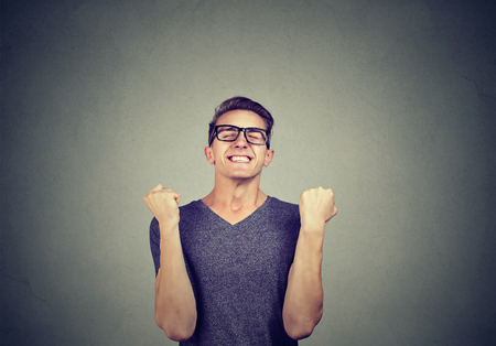 Super excited young man in glasses holding fists in celebration of success Standard-Bild - 110068536