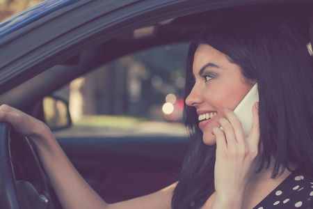 Side view of brunette speaking on phone while driving car cheerfully Imagens