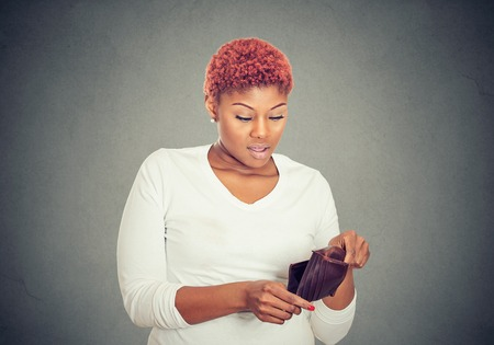 Sad poor young woman showing her empty wallet