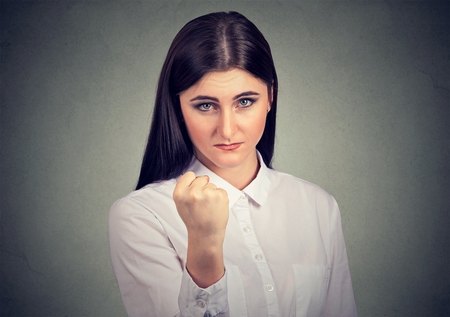 Young brunette wearing formal white shirt and showing fist aggressively at camera Standard-Bild - 110604783