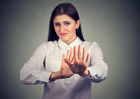Brunette in white shirt outstretching hands in defence and stop gesture looking at camera with disgust Standard-Bild - 110604787