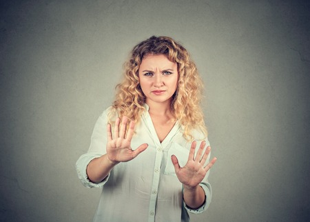 Annoyed offended woman outstretching hands in defence and stop gesture looking at camera with disgust