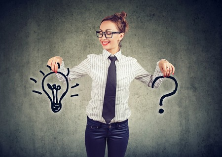 Happy young business woman with question and an answer idea light bulb on gray wall background Фото со стока