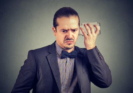 Upset man in looking displeased while listening to rumors with glass jar on gray background