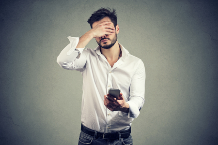 Casual man covering face in despair having bad news on smartphone against gray background Reklamní fotografie