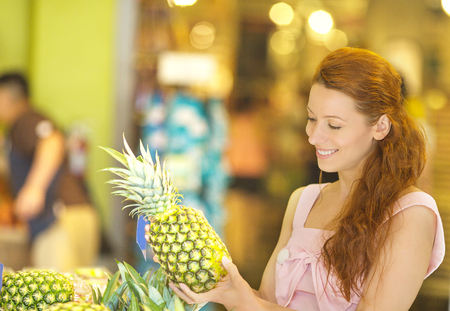 Charming young woman choosing pineapple while shopping in grocery store